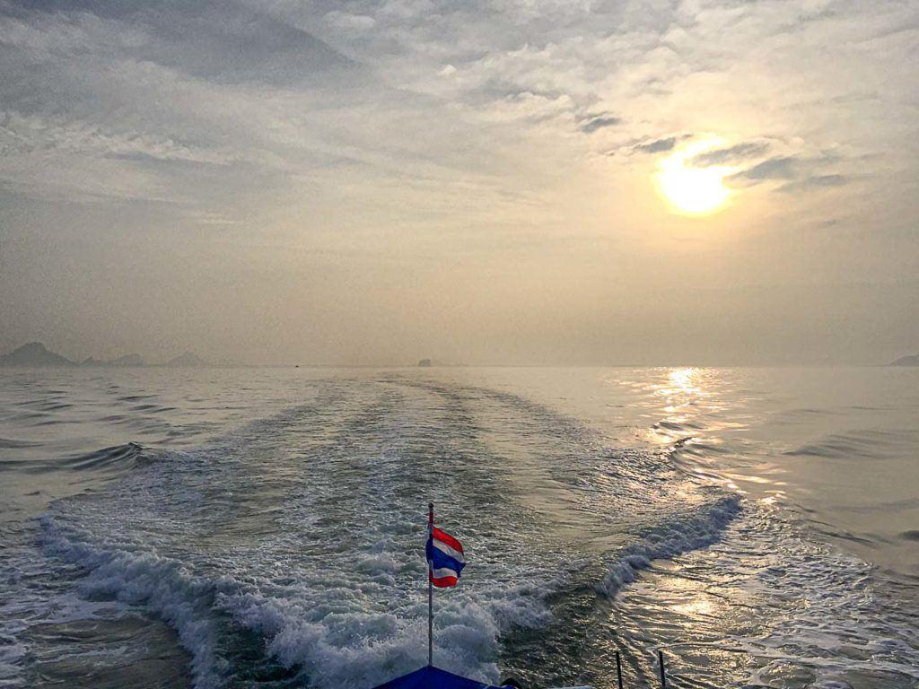 Barco cruzando o mar entre as ilhas tailandesas.