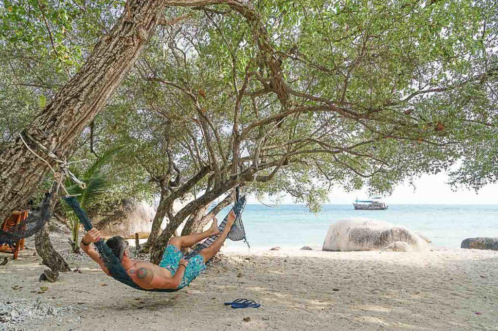 Man resting in hammock at the beach.