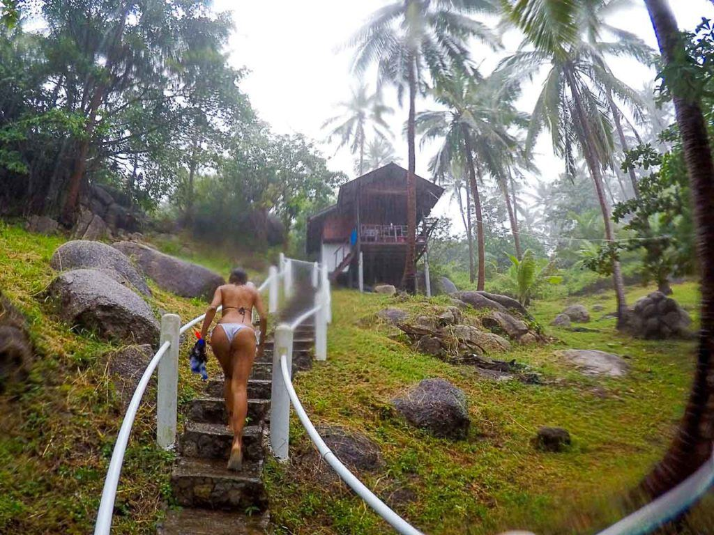 Woman climbing stairs to a bungalow in Freedom Beach.
