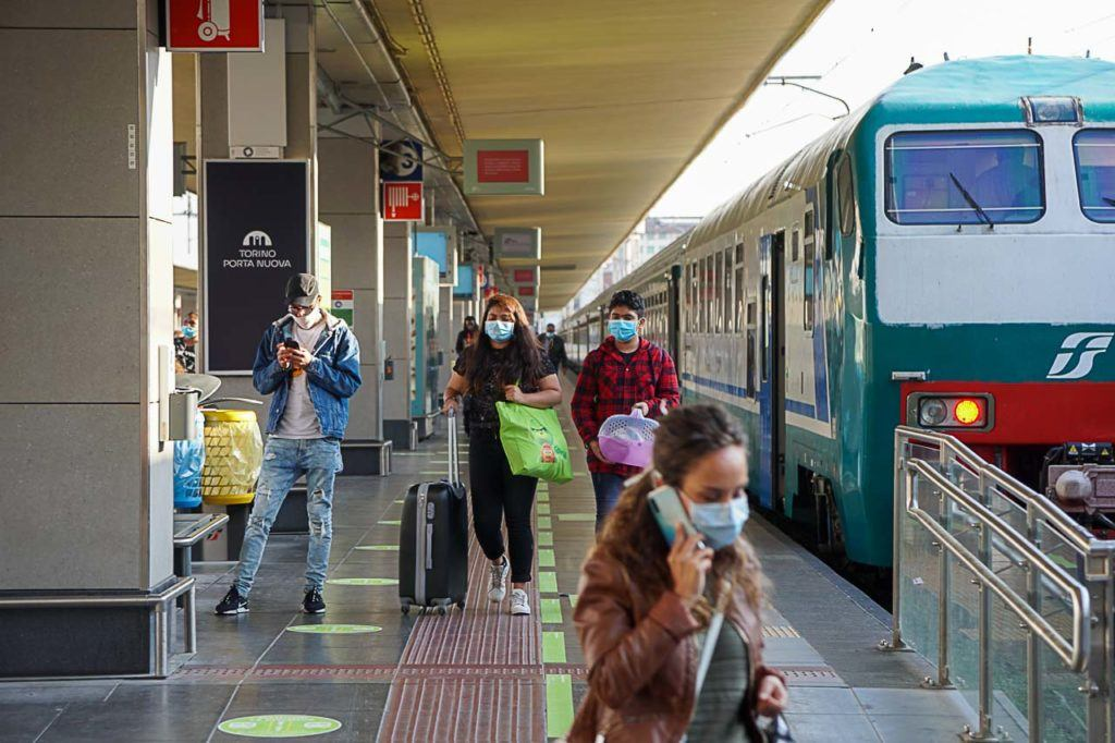 Travelers using facing masks arriving in Turin train station.