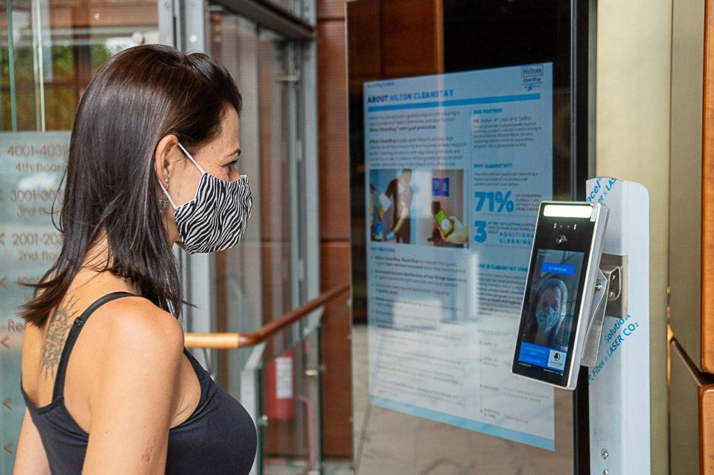 Women having her temperature measure at the entrance of the hotel in Turin, Italy.