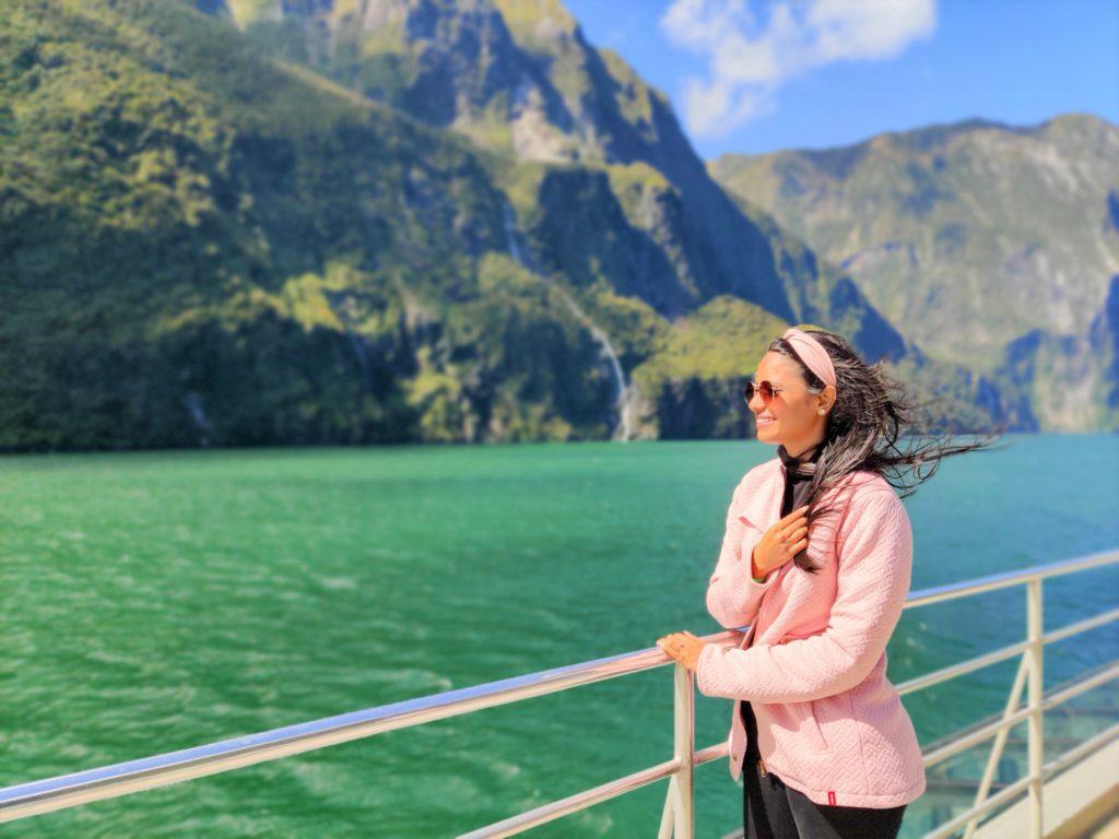 Woman enjoying a cruise trip to Milford Sound, one of the best activities to do in New Zealand.
