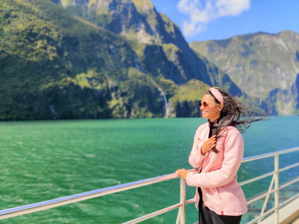 Viajante desfrutando passeio de cruzeiro no Milford Sound, uma das atividades que você deve planejar antes de começar sua viagem à Nova Zelândia.