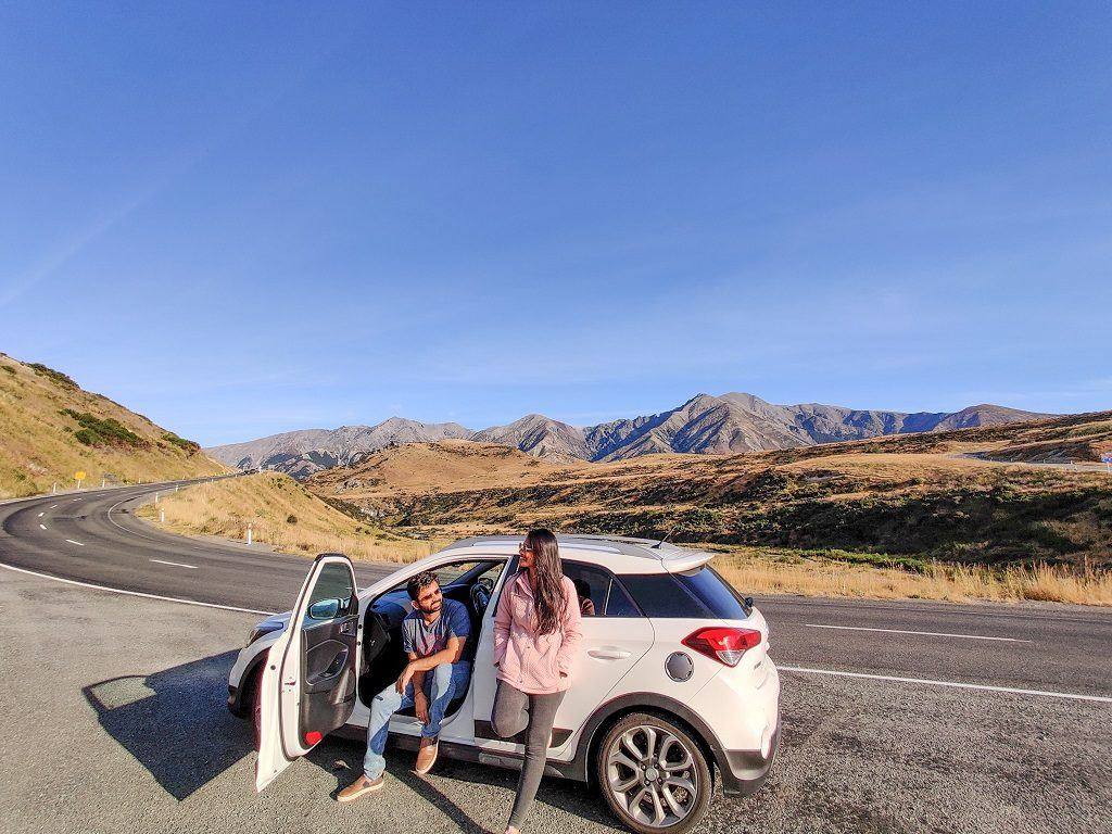 Couple standing in front of car on New Zealand road.