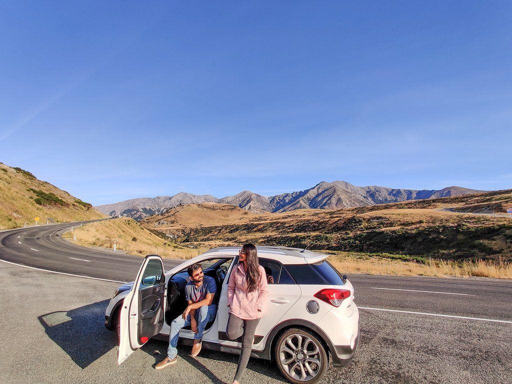 Casal posando para foto em frente ao carro alugado em uma estrada deserta cercada por montanhas na Nova Zelândia.