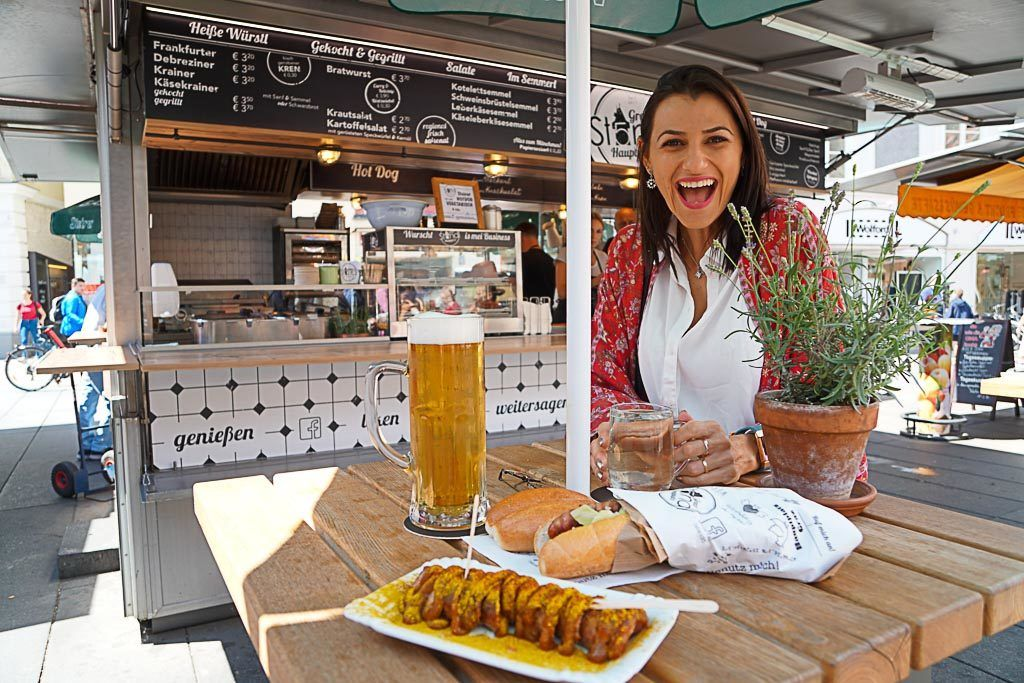 A woman at a food stall in Graz, Austria. She is smiling because she's eating delicious street food and saving money while traveling. There are two hot dogs and a beer on the table.