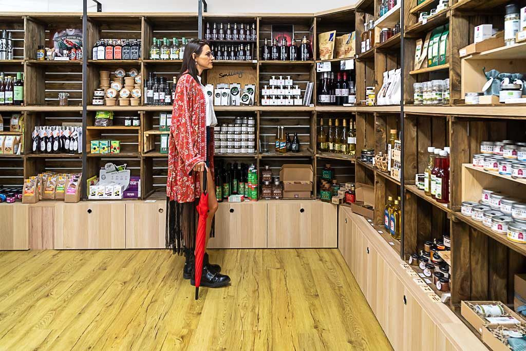 Woman wearing a red coat looking at the shelves of a shop. She is thinking how to save money while traveling, then she won't buy anything.