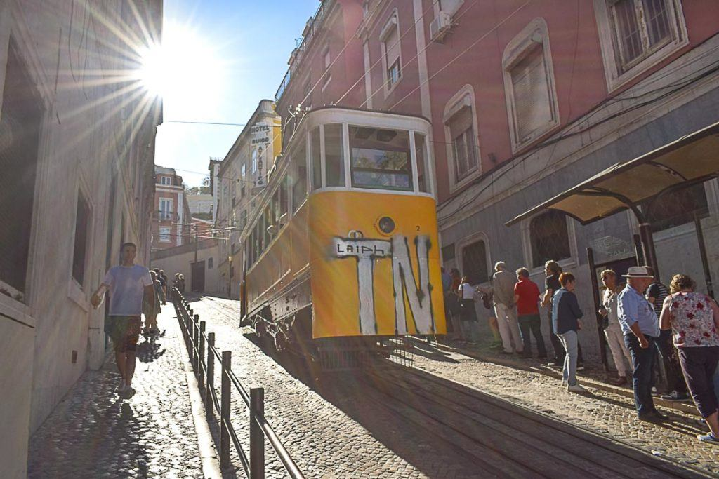 The iconic yellow trams from Lisbon, Portugal. The photo shows a tram passing through a tiny street uphill.