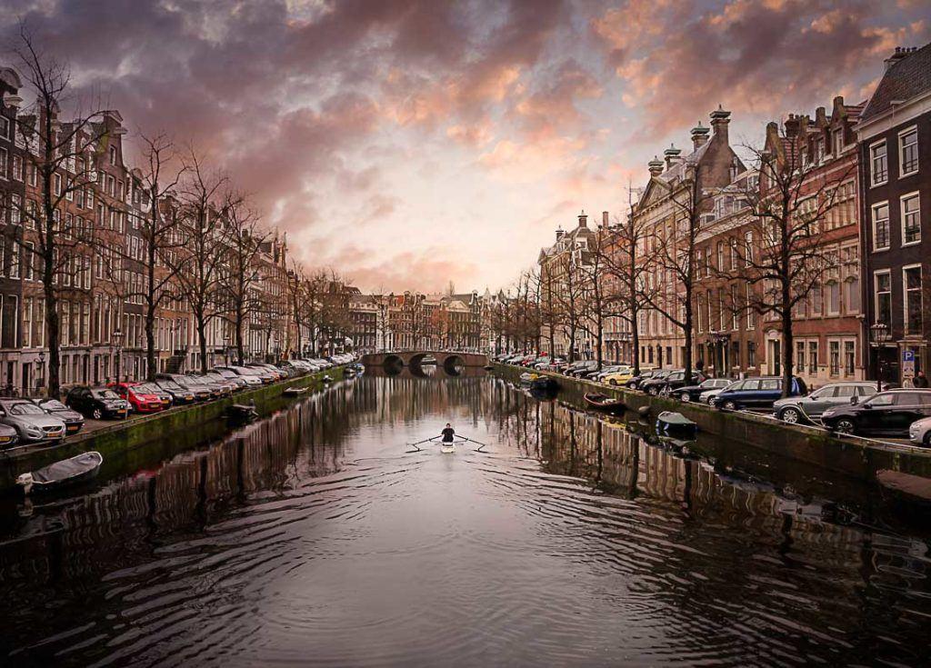 Um homem remando seu barco em um canal de Amsterdam. Descubra aqui quanto custa viajar para Amsterdam e como economizar.