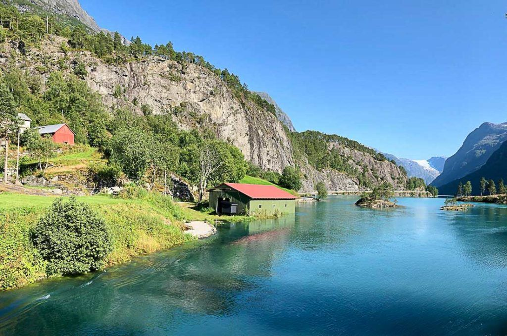 A house by the lake in Norway surrounded by mountains. Explore this article and discover all the information you need to plan a daily budget for your holiday in Norway.
