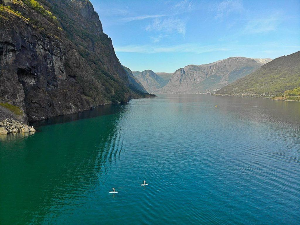 Two people on stand up paddle boards on a lake by the mountains in Norway. Activities in Norway can take a good chunk of your travel budget, plan yours with the help of this Norway Travel Budget Guide.