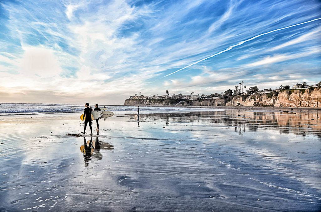 Sunset at the beach of San Diego with surfers. Discover all the information you need to plan your San Diego trip budget .