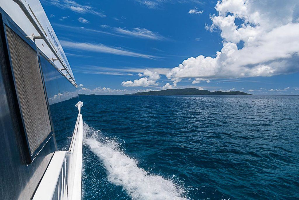 A photo taken from a boat with an island in the background in Seychelles. Planning a trip to Seychelles? Find all Seychelles travel costs here, from activities, food and drinks to transport and accommodation, we've covered it all in this post.