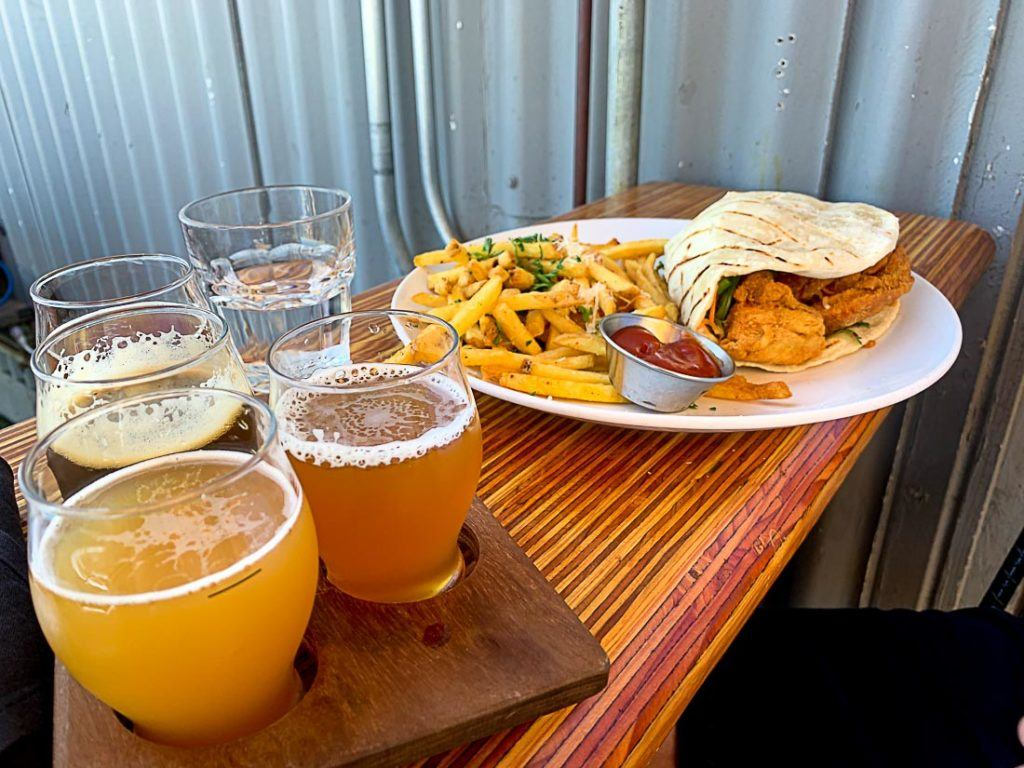 A plate of food and some beers over a table. In this article we talk about all costs of traveling in San Diego, California. Prices of food, drinks, transport, accommodation and attraction that will make your trip budget planning much easier.