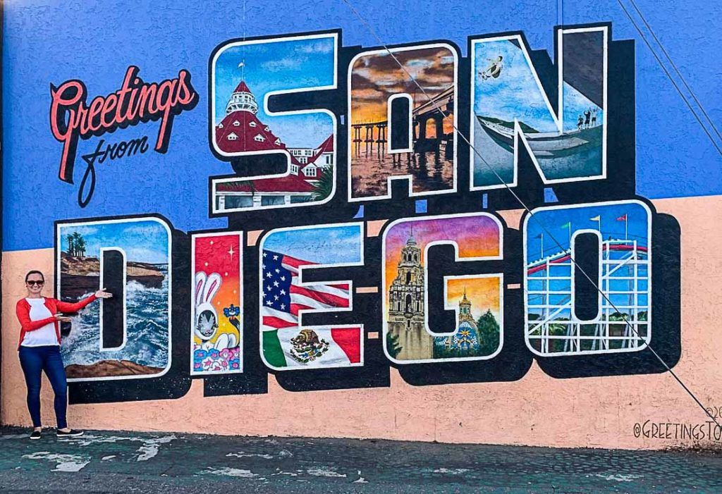 A woman in front of a mural saying 'Greetings from San Diego'. All you need to know about the cost of traveling to San Diego, California, is here. A detailed guide about San Diego travel costs, from hotel prices to transportation, and how to save money on attractions.