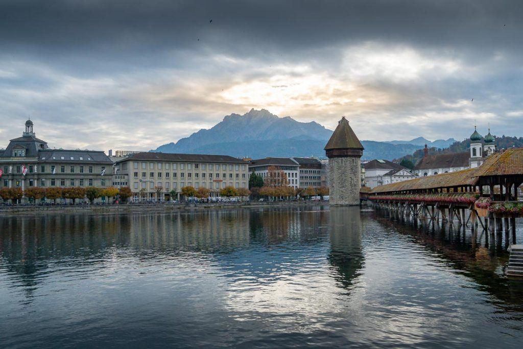Alguns edifícios, a ponte Kapellbrücke, o rio e montanhas ao fundo em Lucerna, Suíça.