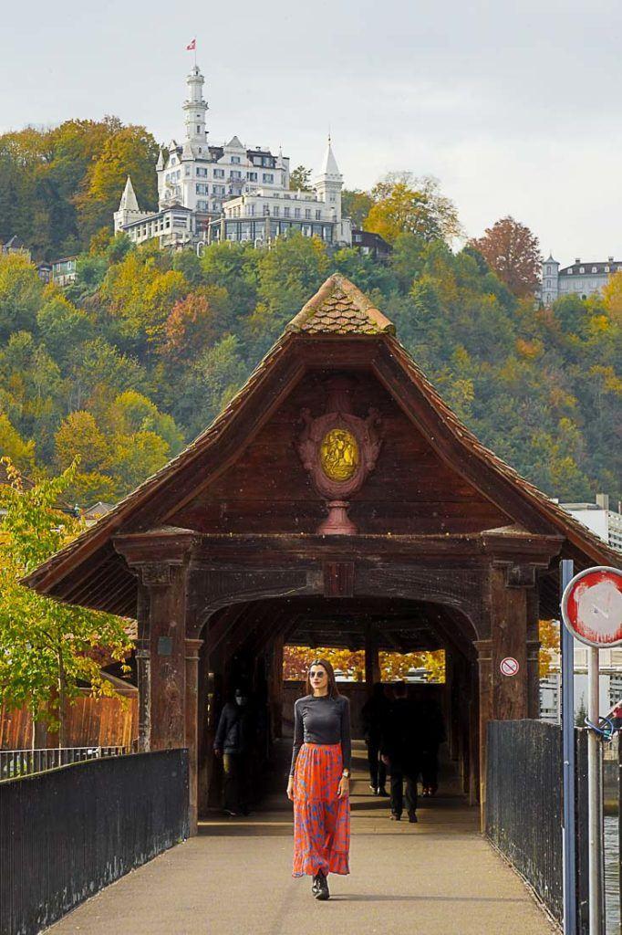 Uma mulher caminhando sobre a Ponte de madeira em Lucerna, Suíça.