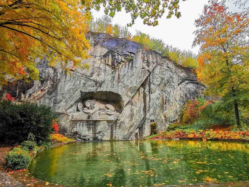 Uma foto do Monumento do Leão com um lago e algumas árvores ao redor.