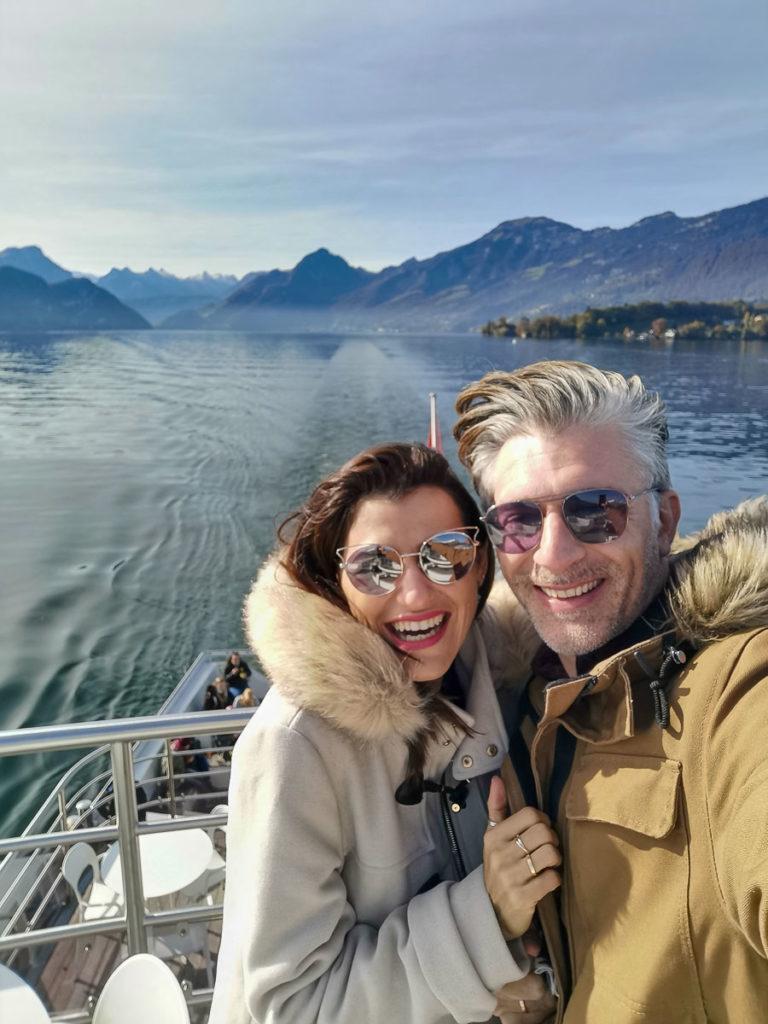 Uma selfie de um casal sorrindo em um passeio de barco no Lago Lucerna.