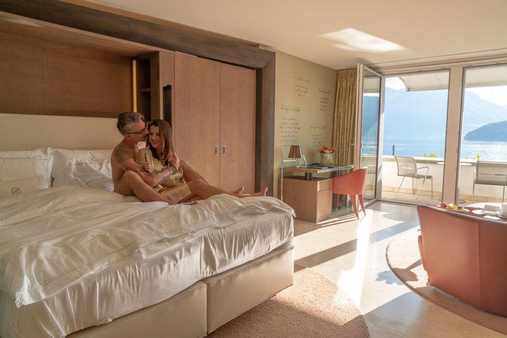 Um casal sentado em sua cama no Park Hotel Vitznau em Lucerna, um dos melhores hotéis da Suíça.