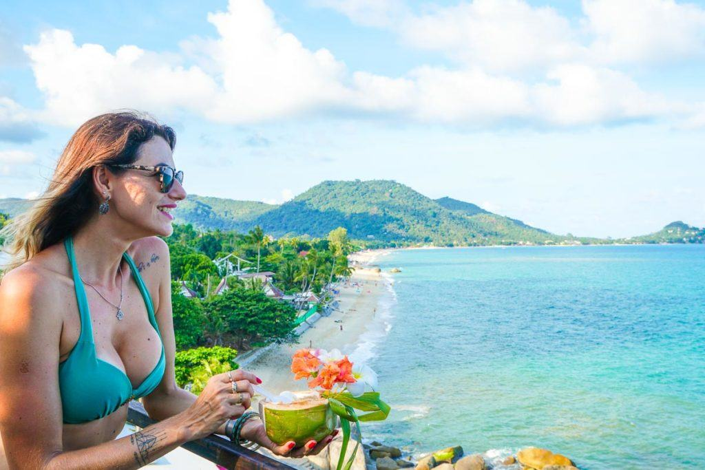 Woman looking at Lamai Beach in Koh Samui while eating a coconut ice cream.