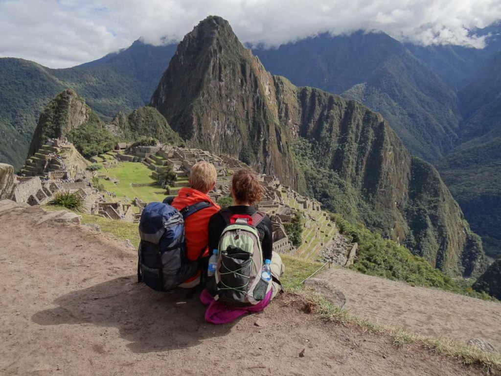 Young couple admiring the ruins of the famous Inca city Machu Picchu in the sacred Urubamba valley near Cuzco in Peru.