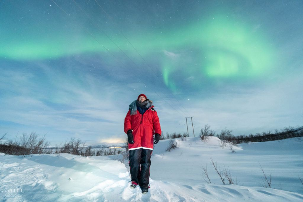 Woman walking on the snow in Tromso, Norway, with northern lights above her.
