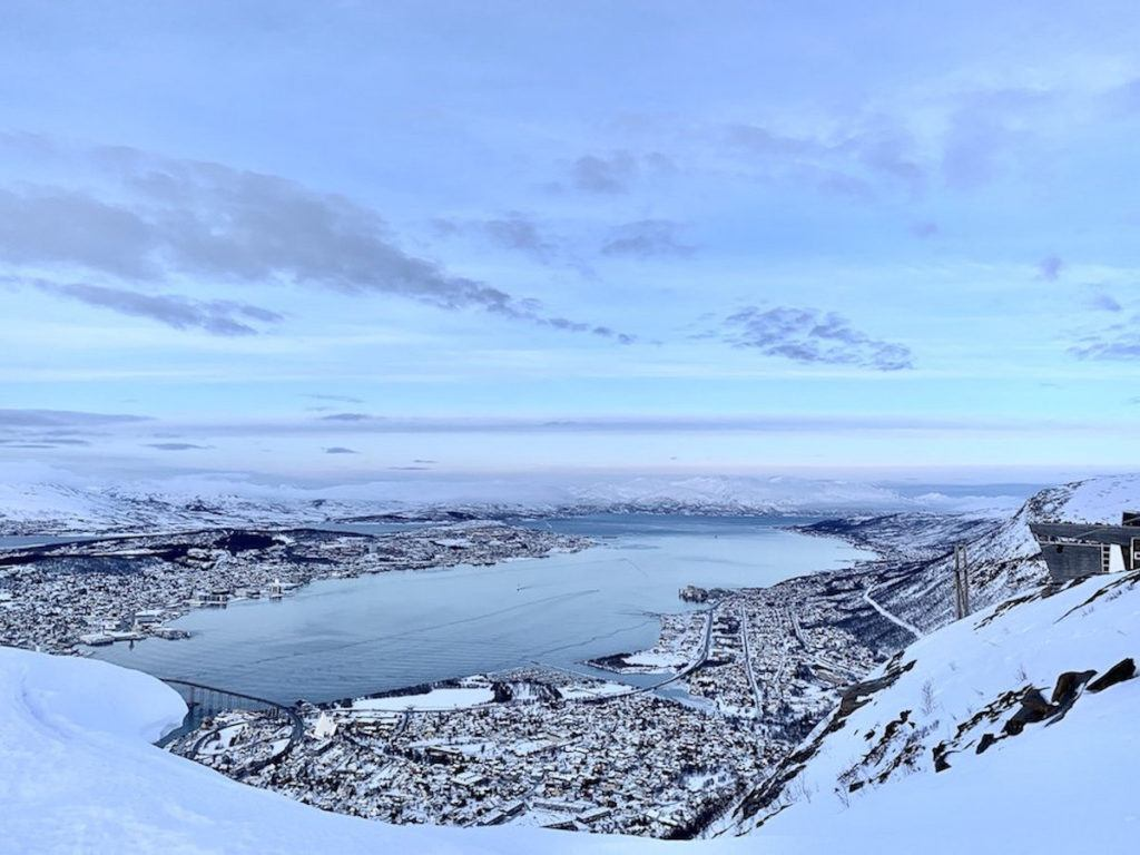 Views from the cable car in Tromso, Norway. You can see the city and mountains covered in snow.