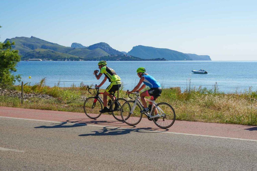 Two cyclists riding along the beach in Mallorca, Spain. One of the top destinations for cycling holiday in Europe.