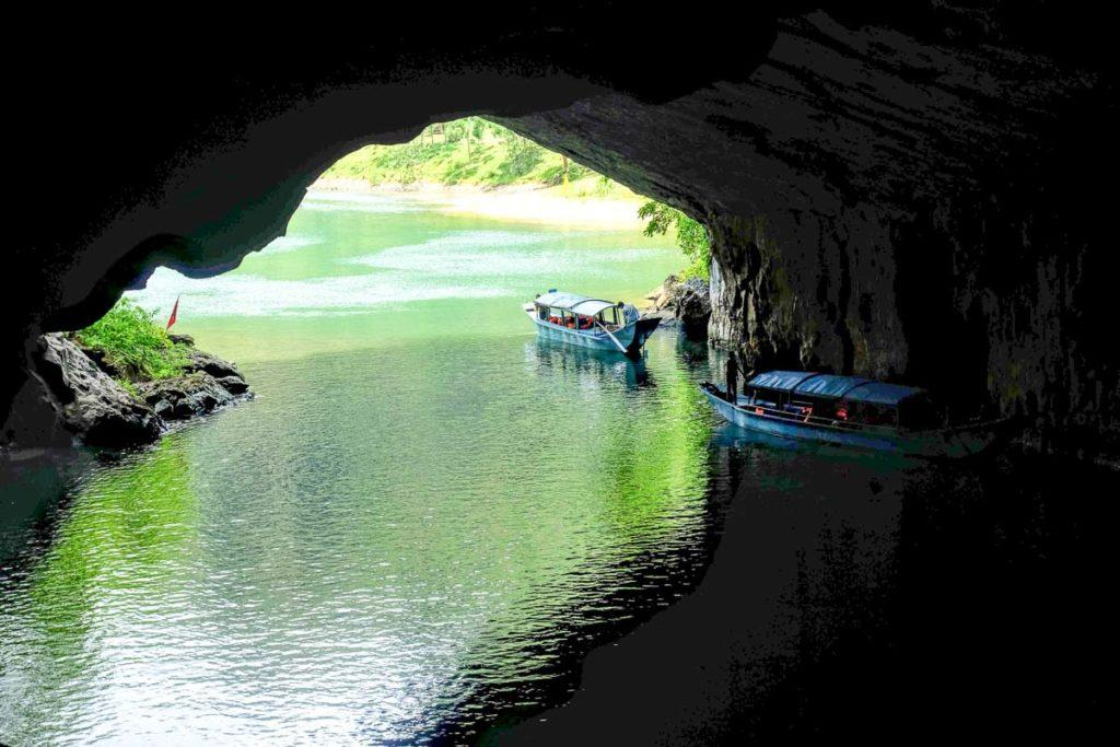 Photo of a cave near a beach with two small boats getting inside the cave. Many people travel to Vietnam to visit the caves.