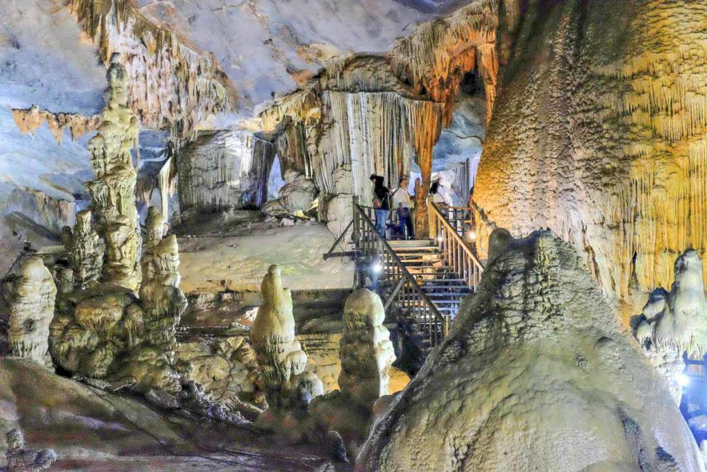 Photo of a karst cave in Vietnam. A huge rocky chamber with stairs and two people inside it.