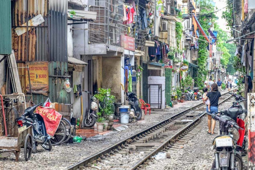 Photo of a train track in between houses and buildings. It's one of the famous attractions in Hanoi, Vietnam.