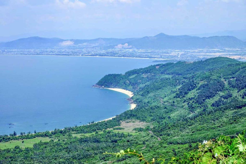 Photo from a viewpoint showing Vietnam's coast with white sand beaches and lush green forest. Vietnam is known for its beaches and islands.