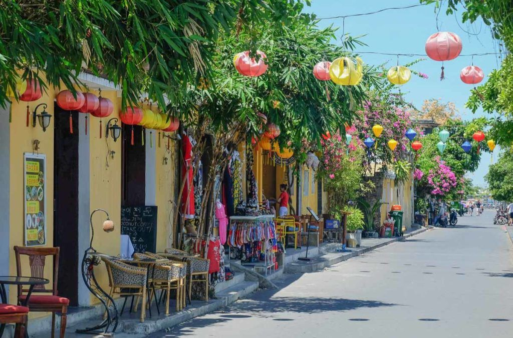Photo of a tiny street in Hoi An with colored lanterns hanging over the street. The shops have many dresses and clothes hanging on their doors. Hoi An is a famous destination in Vietnam.