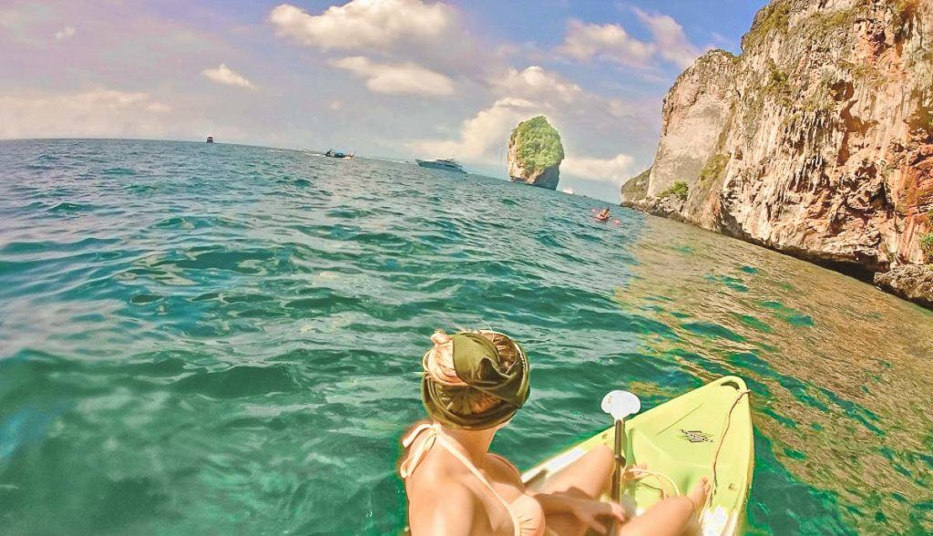 Woman kayaking in crystal clear sea in Thailand, near some limestone formations.