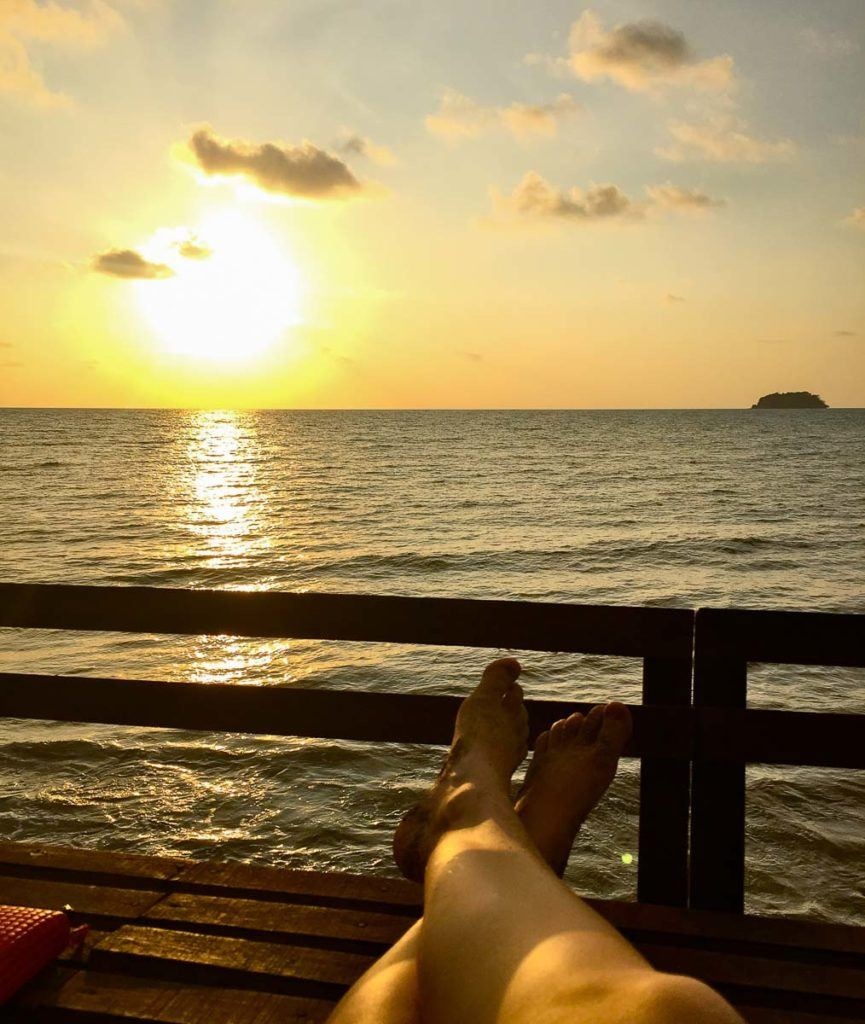 Watch the sunset is one of the top things to do in Koh Chang, Thailand. Here you can the legs of a man on a deck in front of the sea. The sun is setting in the background over the water.