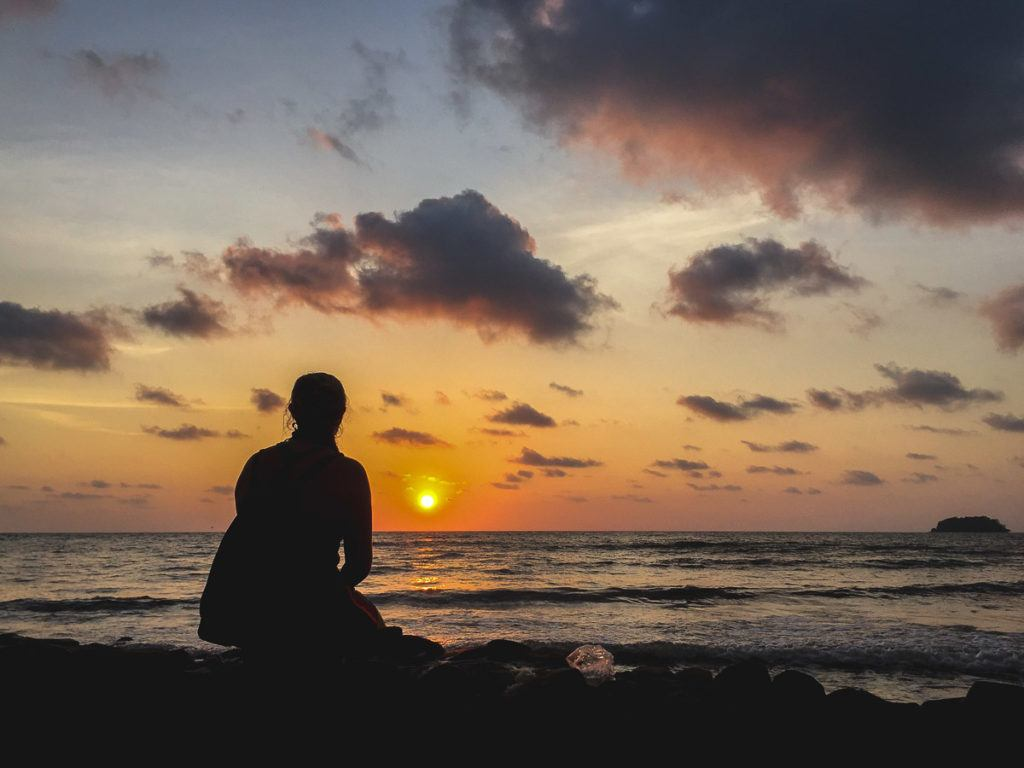 Photo of a woman sitting on Koh Chang Beach watching the sunset.