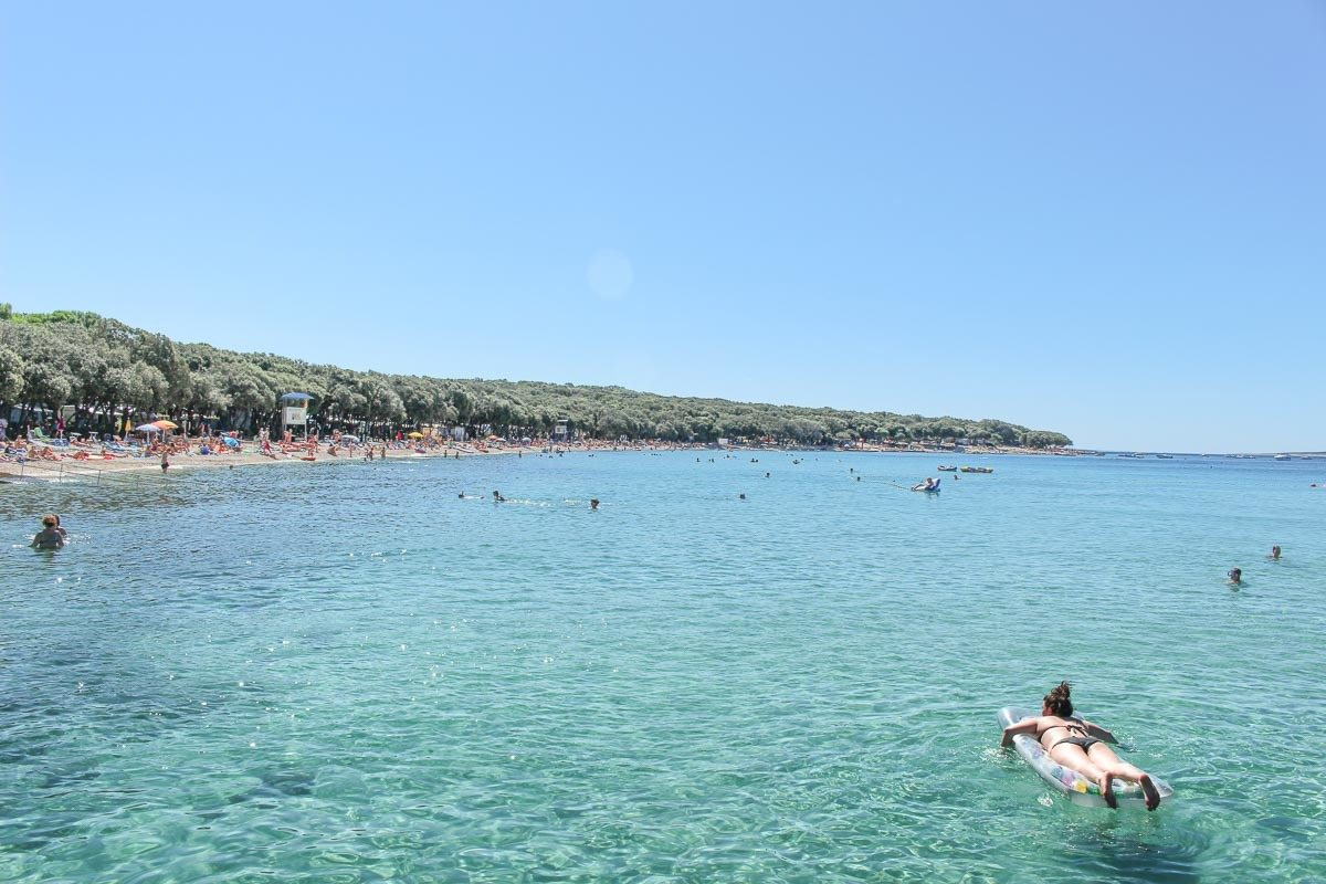 A beach in one of the best Croatian Islands. There are people in the water and many tress by the sand.