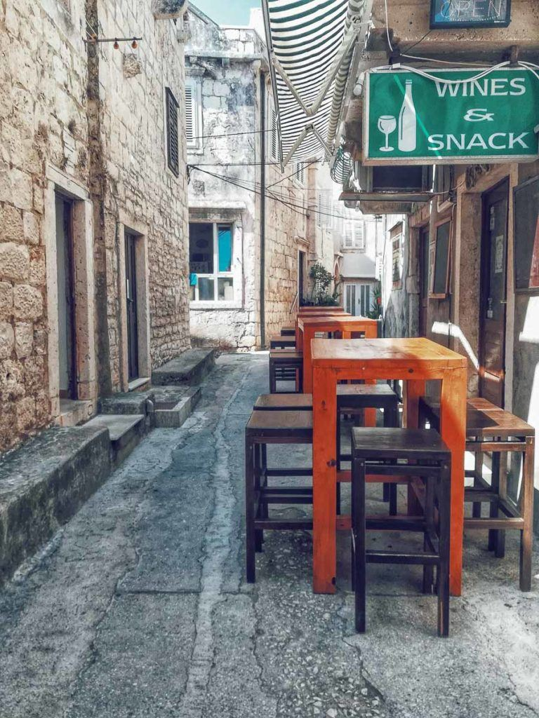 Korčula Island is famous for its food and wine. The photo shows a few outdoor tables in front of a local Croatian restaurant.