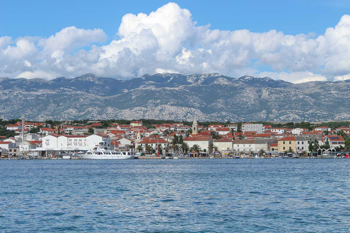 Photo of a town on an island in Croatia. The photo was taken from the boat, you can see the houses in the front and the mountains in the back.