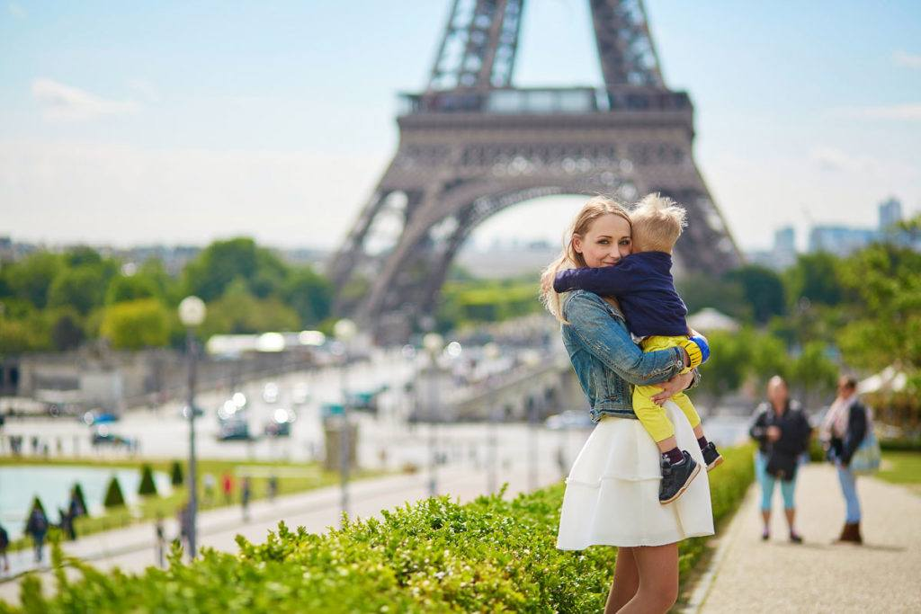 Woman holding carrying a little boy in front of the Eiffel Tower in Paris, France. She is an au pair in France.
