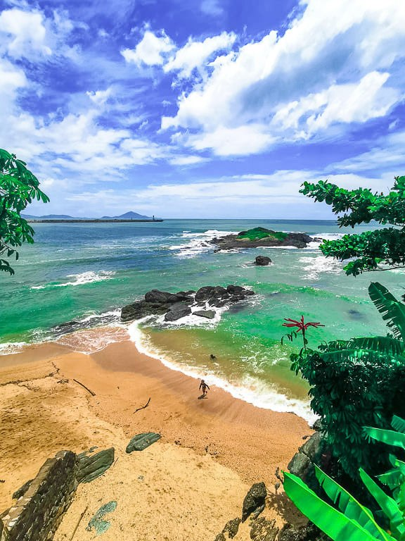 Photo of a tropical beach in Santa Catarina, Brazil. You can see the emerald green sea and the lush green vegetation by the beach.