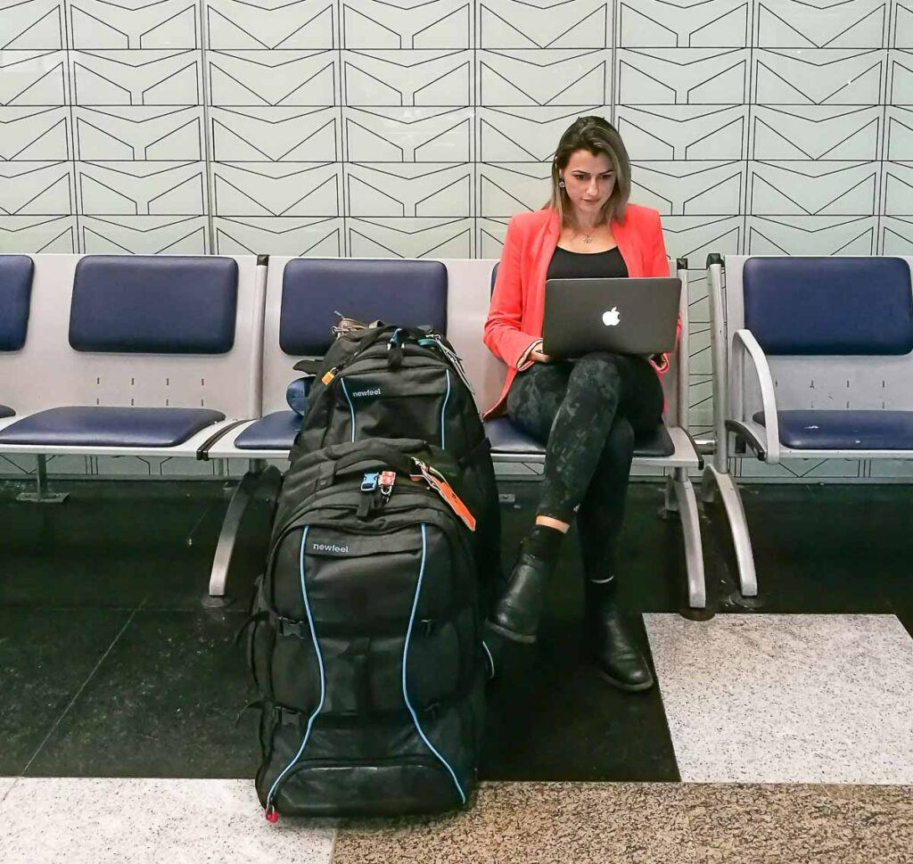 A woman is using a laptop at the airport. She is using the airport wifi to connect to the internet to work online. This is one of the advantages of traveling with a laptop.